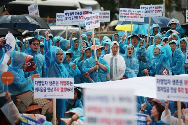 Angry self-employed businessmen from across the country call for the government to revoke the recent sharp increase of the minimum wage during a rally amid heavy rains at Gwanghwamun Square in downtown Seoul on Aug. 29, 2018. Many self-employed persons gave up their businesses in the wake of the hike. Photo by Yonhap