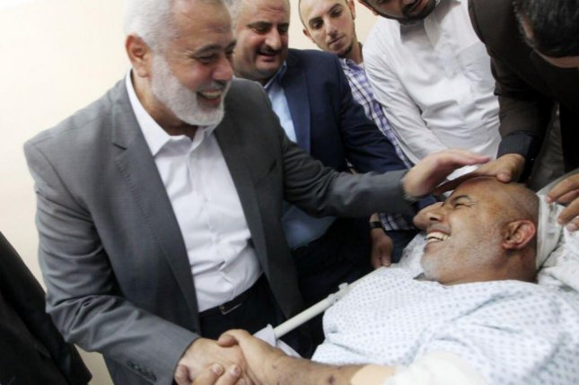 Ismail Haniyeh, president of the Hamas politburo in Gaza, L, visits the hospitalized Tawfiq Aby Naim, R., head of Gaza security on Friday. Naim was hospitalized after a car bomb explosion. Photo courtesy of Hamas/Twitter