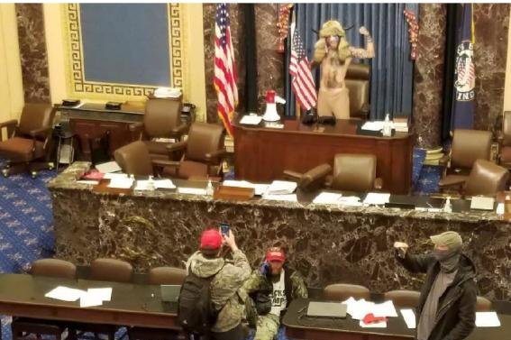 Jacob Anthony Chansley is shown standing at the dais in the U.S. Senate chamber on January 6 during the riots at the U.S. Capitol. This image from Twitter is part of the U.S. Department of Justice's complaint.