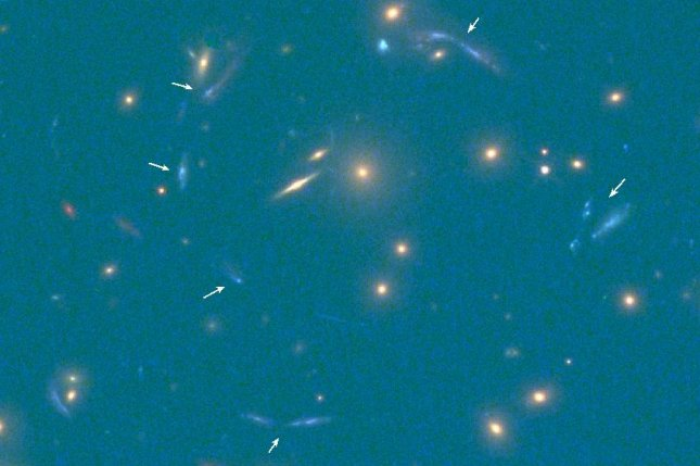 White arrows reveal multiple iterations of the distant galaxy's light. Lensing yields multiple images of the galaxy, organized in a ring around the intermediary source of light-warping gravity. Photo by Hubble Space Telescope