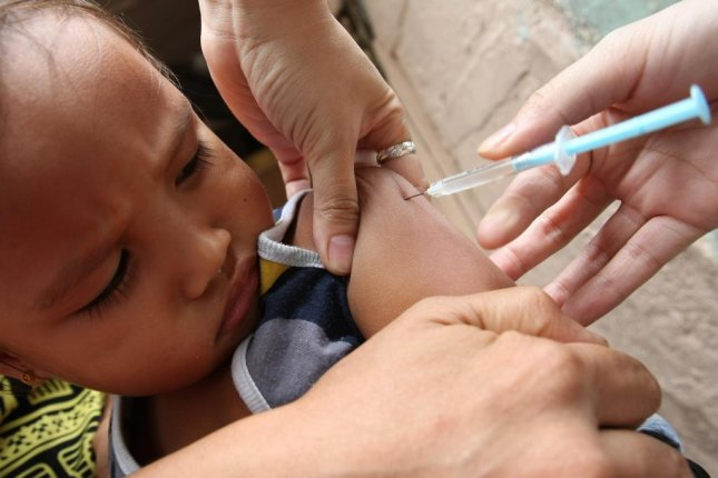 A child receives a shot of measles vaccine during the house to house campaign against measles conducted by the Department of Health in an east suburban of Manila, Philippines. Photo by Val Handumon/EPA