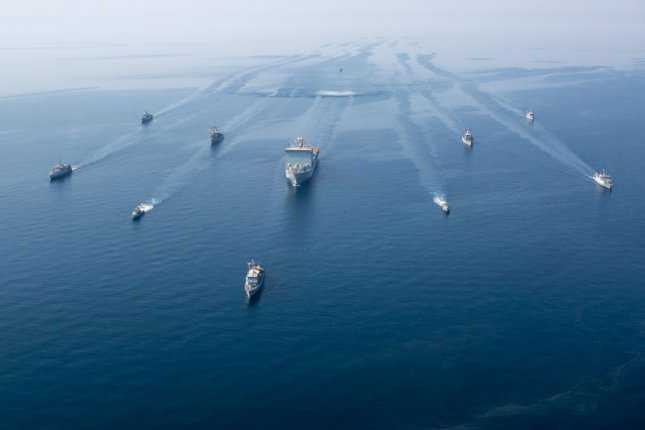A multinational group of mine countermeasure ships from the French Marine Nationale, UK Royal Navy, U.S. Navy and a MH-53E Sea Dragon helicopter operate in formation during exercise Artemis Trident 21 in the Arabian Gulf on April 21. Photo Theoren Neal/U.S. Army