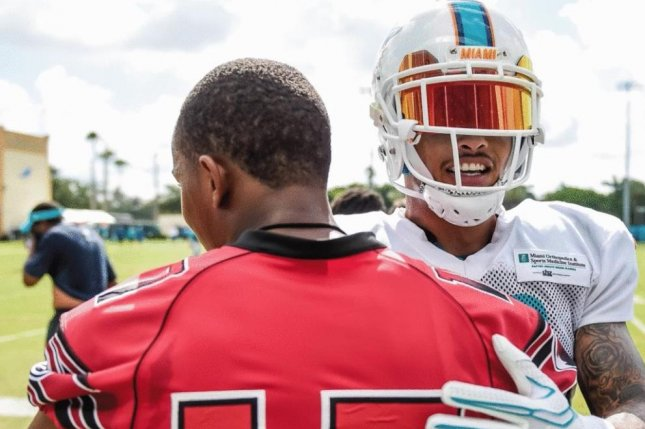 Miami Dolphins wide receiver Kenny Stills (R) hugs a player from Miami Edison High School during a team visit to the team's training facility in 2017 in Davie, Fla.