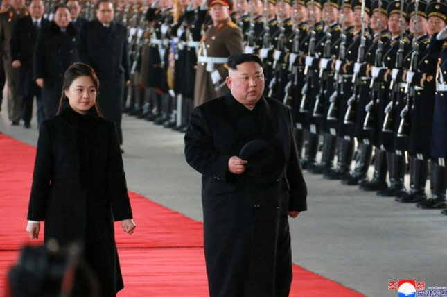 A photo released by North Korean Central News Agency (KCNA) on Monday shows North Korean leader Kim Jong Un (R) and his wife Ri Sol Ju (L) reviewing a guard of honor as he leaves for China from Pyongyang, North Korea. Photo by KCNA/EPA-EFE