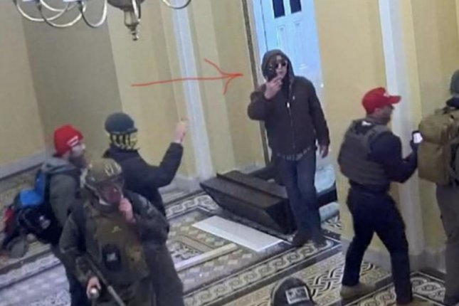 Bryan Ivey can be seen in videos from the Capitol attack wearing a brown, hooded jacket and holding what appears to be a cell phone. Image courtesy of the Justice Department