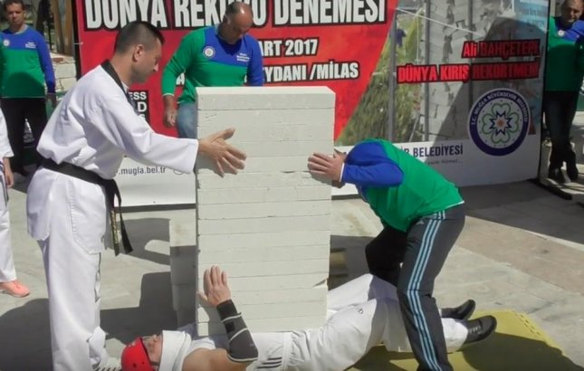 Turkish martial artist Ali Bahcetepe broke his own Guinness World Record by having 16 concrete blocks broken over his chest in 4.75 seconds. Screen capture/Guinness World Records/YouTube