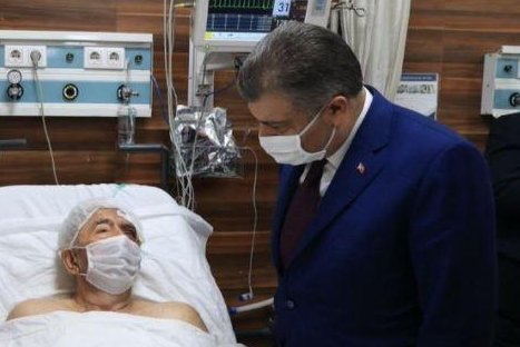 Turkish Health Minister Fahrettin Koca visits Ahmet Citim, 70, in the hospital after being pulled from the rubble 34 hours after an earthquake struck western Turkey. Photo courtesy Fahrettin Koca/Twitter