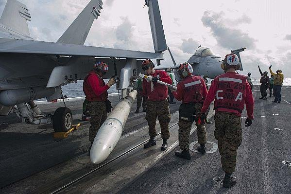 U.S. Marines remove a training AGM-88 High Speed Anti-Radiation Missile from an F/A-18C Hornet on the flight deck of the Nimitz-class aircraft carrier USS Theodore Roosevelt in 2015. Photo by Mass Communication Spec. Seaman Anthony N. Hilkowski/U.S. Navy