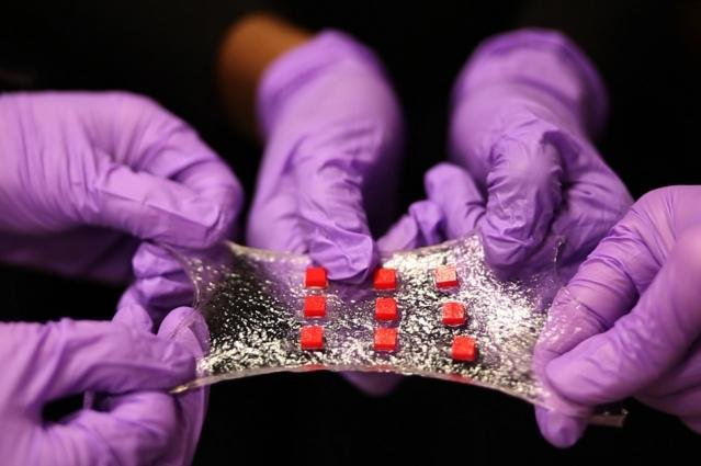 A sheet of hydrogel developed at MIT is bonded to a matrix of polymer islands -- the red squares -- that can encapsulate electronic components such as semiconductor chips, LED lights, and temperature sensors. Photo by Melanie Gonick/MIT
