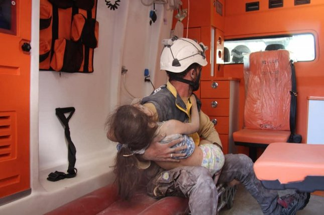 A White Helmets first responder rescues a child in Ariha City in southern Idlib on Monday after six civilians were killed and 20 were injured when Syrian government war planes attacked the city. Photo courtesy White Helmets/Twitter