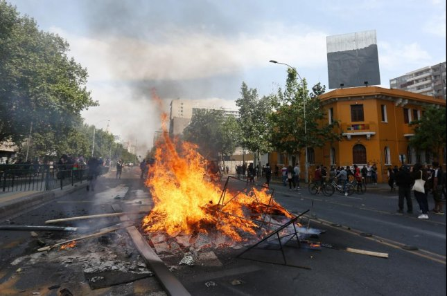People burn objects as demonstrations against the increase of Metro fares take place, in Santiago, Chile Saturday. Chilean authorities called off the price hikes after three people died in a supermarket fire. Photo by Elvis Gonzalez/EPA-EFE