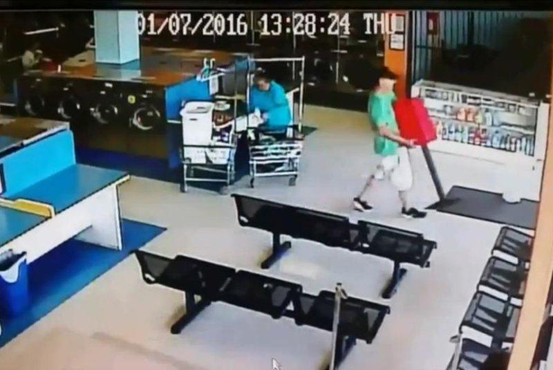 A brazen daylight thief walks off with a laundromat's gumball machine in Dallas. Storyful video screenshot