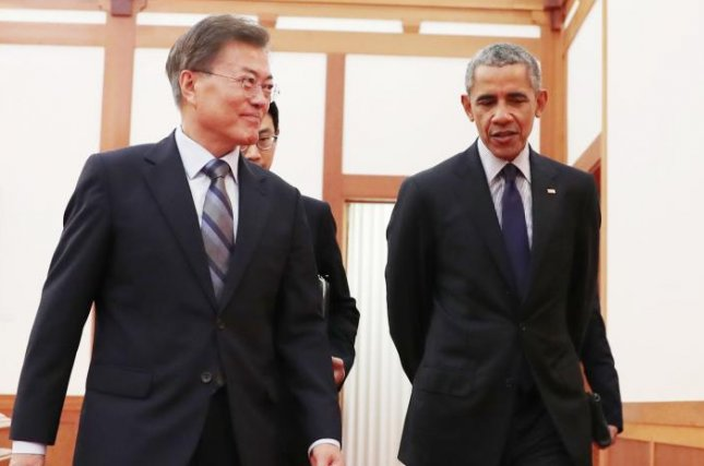 A photo released by the South Korean Presidential Office shows South Korean President Moon Jae-in (L) walking with former U.S. President Barack Obama (R) during their meeting at the presidential office Cheong Wa Dae in Seoul, South Korea on Monday. Photo by Yonhap/EPA