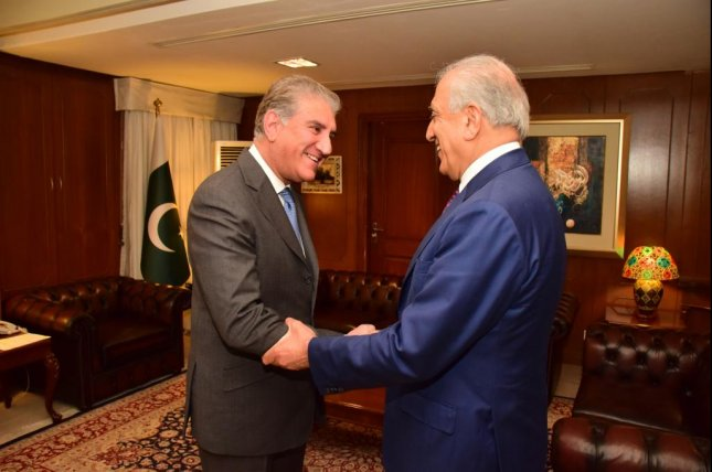 U.S. special representative Zalmay Khalilzad (R) greets Pakistani Foreign Minister Shah Mehmood Qureshi amid peace talks in Islamabad, Pakistan, last week. Khalizad is negotiating a peace deal with the Taliban for U.S. forces to leave Afghanistan. Photo by Foreign Office Pakistan/EPA-EFE