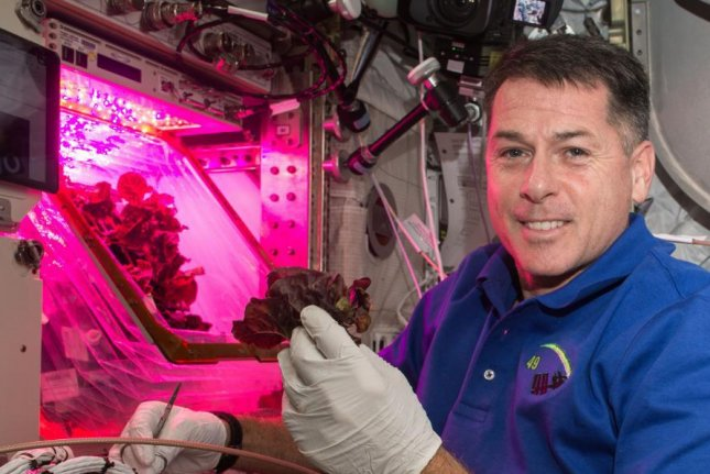 Astronaut Shane Kimbrough holds lettuce in front of the Veggie chamber on the International Space Station in November 2016. Photo courtesy of NASA