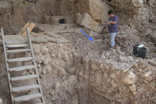 The cave during excavation with the arrow pointing to the hearth. (Credit: Weizmann Institute)
