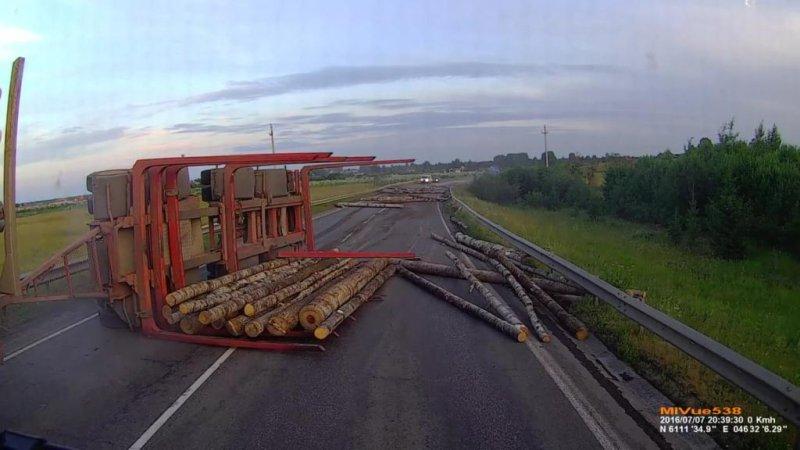 A lumber trailer overturns on a Russian road, sending logs toward a vehicle with a dashboard camera. Screenshot: JukinMedia