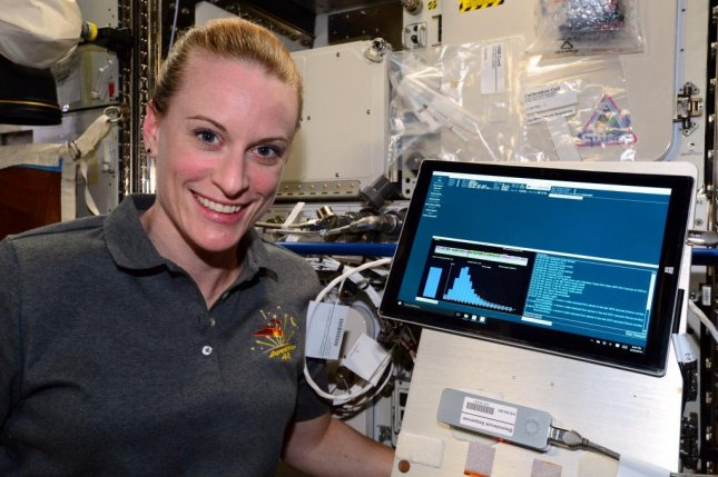 NASA astronaut Kate Rubins poses with MinION, the device that DNA-sequencing possible in space for the first time. Photo by NASA