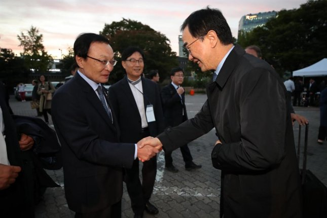 Rep. Lee Hae-chan (L), chief of the ruling Democratic Party, shakes hands with Unification Minister Cho Myoung-gyon in Seoul on Thursday. Photo by Yonhap