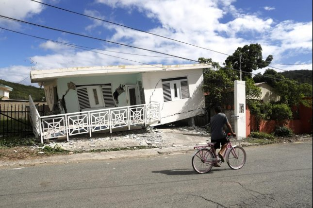 A bicyclist passes a house damaged by a strong earthquake Monday on the coast of Guanica, Puerto Rico. A stronger quake rattled the island territory Tuesday. Photo by Thais Llorca/EPA-EFE