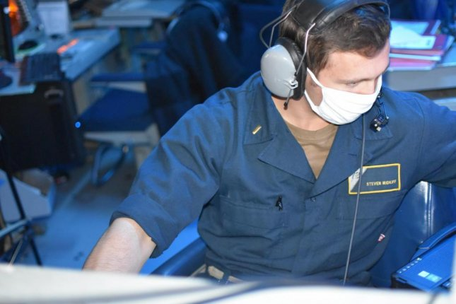 Ensign Steven Midkiff monitors communications in the combat information center aboard guided-missile cruiser USS Port Royal during a joint air defense exercise in the Gulf of Oman on Sunday. Photo courtesy U.S. Navy