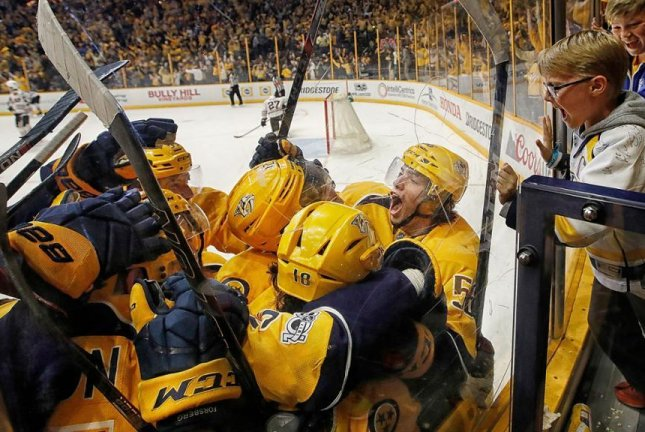 Teammates mob Kevin Fiala after his game-winning OT goal Monday night against Chicago, giving Nashville a 3-0 series lead. Photo courtesy NHL.com