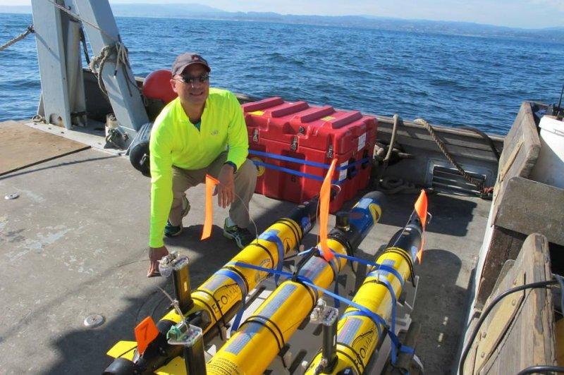 NASA scientist Steve Chien poses with three underwater drones on Monterey Bay. Photo by NASA/JPL/Caltech