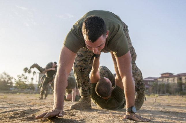 U.S. Marine Corps Capt. Joshua P. Hays, a communications strategy and operations officer with the 13th Marine Expeditionary Unit, I Marine Expeditionary Force, executes a pistol belt drag with Maj. Andrew T. Macon, an artillery officer with the 13th MEU, I MEF, during a unit physical training event at Camp Pendleton Calif., in 2019. Photo by Van Fredenberg/U.S. Marine Corps