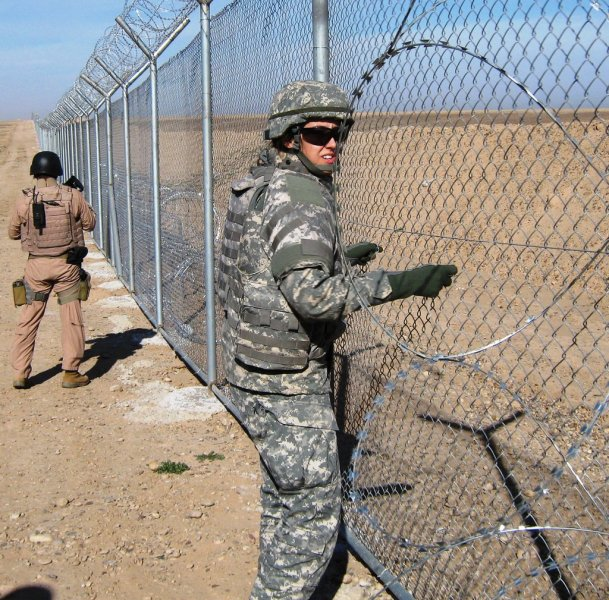 Elizabeth Burg, project engineer for the U.S. Army Corps of Engineers, at the fence of the Pipeline Exclusion Zone, 35 miles northwest of Baghdad. (Photo courtesy Elizabeth Burg.)
