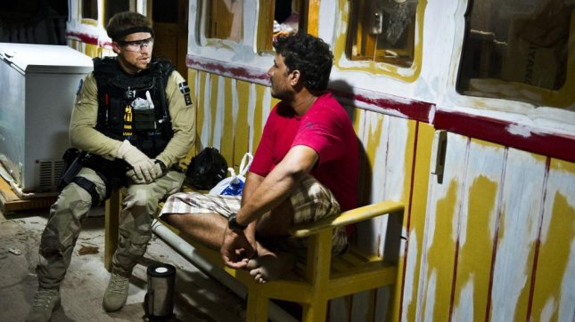 Crewmember of EU Naval Force warship HSwMS Carlskrona speaks with Indian sailor about their ordeal in the hands of pirates. (EU Navy)