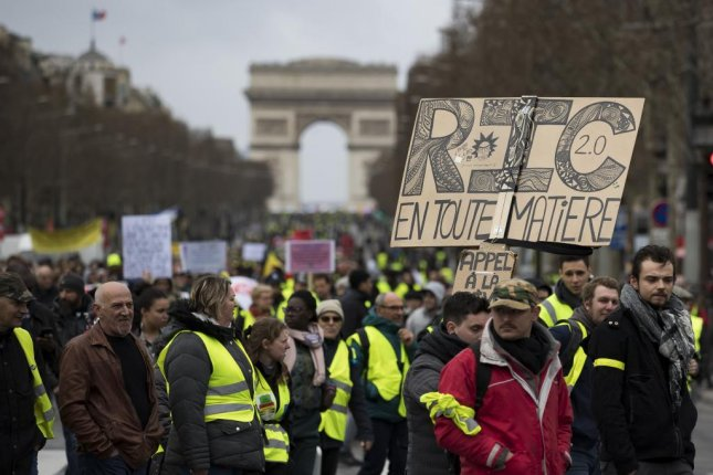 Protesters from the 'Gilets Jaunes' (Yellow Vests) movement walk down the Champs Elysees avenue near the Arc de Tiomphe during the 'Act XVII' demonstration in Paris, France, March 9. The protests turned violent with fires and vandalism on Saturday. Photo by Ian Langsdon/EPA-EFE