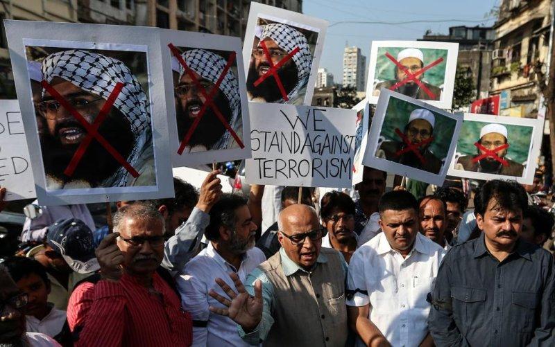 Protesters hold placards against Pakistan's Jaish-e-Mohammedhead Masood Azhar (L), and head of the banned Islamic charity Jamat-ud-Dawa, Hafiz Saeed (R). Photo by Divyakant Solanki/EPA