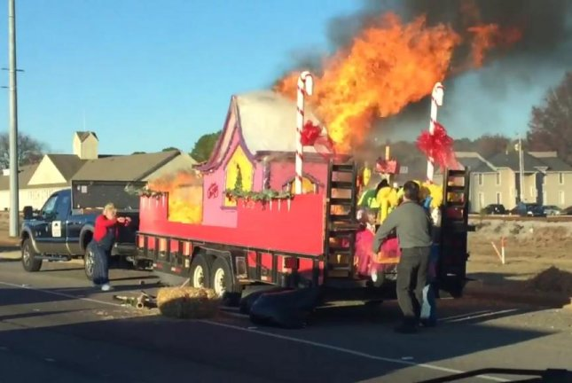A Grinch-themed parade float in Alabama burns after being struck by a cigarette butt tossed from a passing vehicle. Screenshot: WHNT-TV