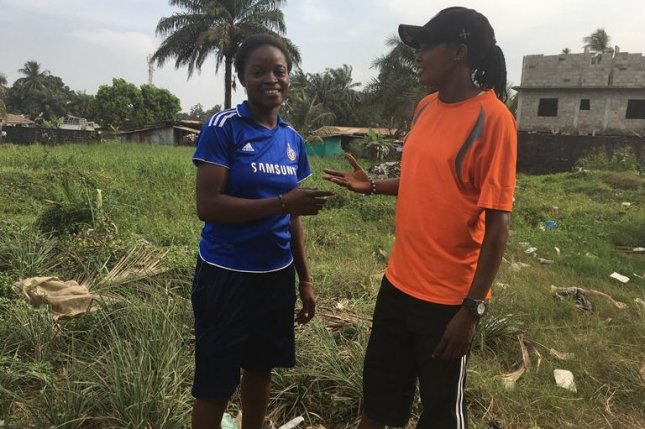 Joy Kollie (R) and her sister Love (L) prepare for a run in the Monrovia suburb of Chocolate City. Photo by Kate Thomas/Women & Girls