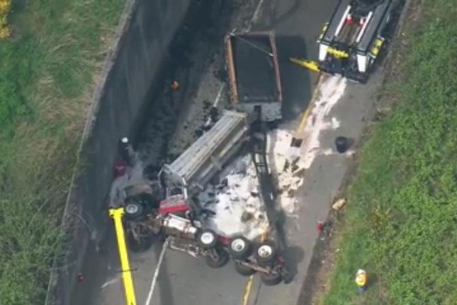 An overturned semi trailer covers Interstate 5 in human waste. Screenshot: KOMO News/Facebook