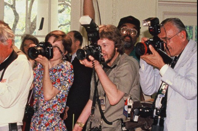 Leighton Mark (C) uses a camera designed specifically for one-handed use in the Oval Office of the White House in 1985. Mark died Saturday at the age of 67. File Photo by Dennis Brack
