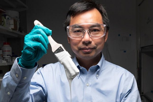 Xiulin Ruan, a professor of mechanical engineering at Purdue University, shows off the paint that was declared the world's whitest by Guinness World Records. Photo courtesy of John Underwood/Purdue University