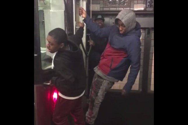 Three teenagers cling to the back of a New York subway train as it departs a station in the Bronx. Screenshot: Alex Campos/Facebook