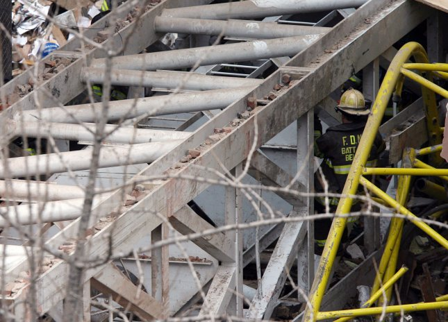A New York City firefighter works under a section of a crane that collapsed March 15, 2008. The crane crashed into buildings. Seven people were killed and many others injured. File Photo by John Angelillo/UPI