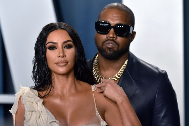 Kim Kardashian (L) and her husband Kanye West arrive for the Vanity Fair Oscar party on February 9. Kardashian has signed an exclusive deal with Spotify to release a podcast series. File Photo by Chris Chew/UPI