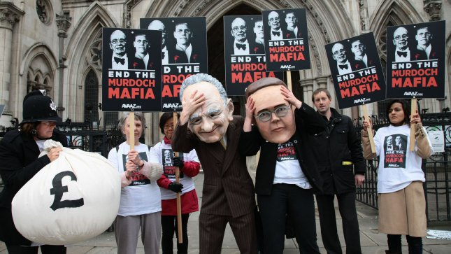 Protesters from the campaign group Avaaz demonstrate outside the High Court with large James and Rupert Murdoch masks as former News International Chairman James Murdoch gives evidence to the Leveson Inquiry in London on Tuesday April 24 2012.The Leveson Inquiry is currently concentrating on the owners of various media groups. Rupert Murdoch,owner of News Corp will be giving evidence to the Inquiry tomorrow. UPI/Hugo Philpott