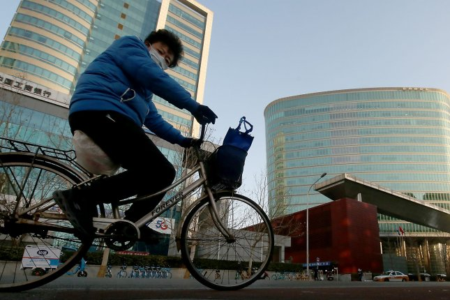 A Chinese woman cycles past China National Offshore Oil Corporation's headquarters in Beijing on Saturday. Mainland China is on high alert after an outbreak near North Krea. Photo by Stephen Shaver/UPI
