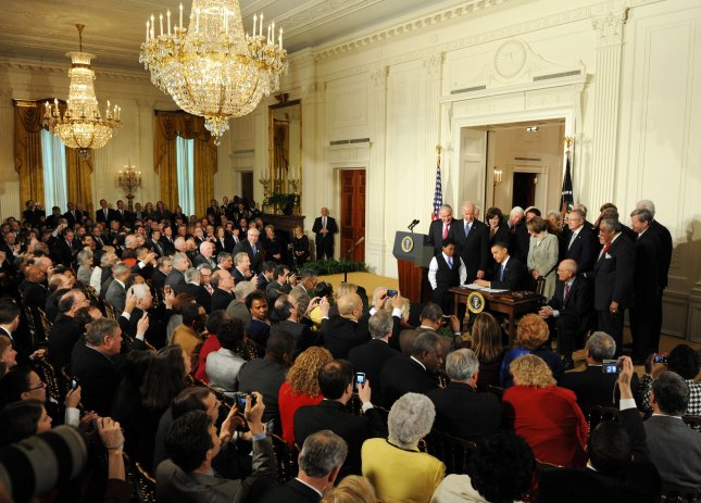 U.S. President Barack Obama signs the Health Insurance Reform Bill surrounded by invited guests and members of congress in the East Room of the White House in Washington, DC on March 23, 2010. The historic $938 million health care bill will guaranteed coverage for 32 million uninsured Americans and will touch nearly every American's life. UPI/Pat Benic