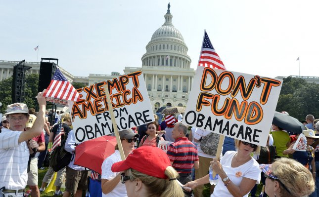 Hundreds of people gather on the grounds of the US Capitol at a Tea Party rally to push for de-funding Obamacare, The Affordable Care Act, on Capitol Hill, September 10, 2013, in Washington, DC. Unable to override votes to defeat President Barack Obama's health care act, some Congressional Republicans are hoping to end funding for it. UPI/Mike Theiler