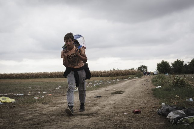 At least 17 migrants drowned on Sunday when their boat sank. More than 500,000 migrants have gained entry into the European Union to escape war and poverty. Pictured: A young boy crosses into Croatia from a road that passes through corn fields near the border town of Tovarnik, Croatia on September 20, 2015. Photo by Achilleas Zavallis/UPI
