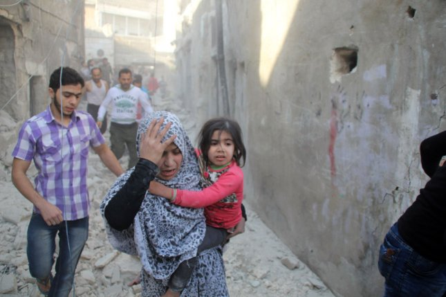 A Syrian woman carries her child as she is looking for her relatives in the rubble of destroyed houses following what local activists say was an airstrike by Russian in the rebel-held area of Kallasah, outskirts of Aleppo, Syria. North Korean troops are in Syria, according to a Syrian opposition delegate in Geneva. Photos by Ameer Alhalbi/ UPI