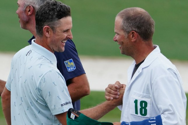 Justin Rose (L) shakes hands with his caddie, David Clark, on the 18th green after finishing at 7-under par in the first round of the 2021 Masters Tournament on Thursday at Augusta National Golf Club in Augusta, Ga. Photo by Kevin Dietsch/UPI