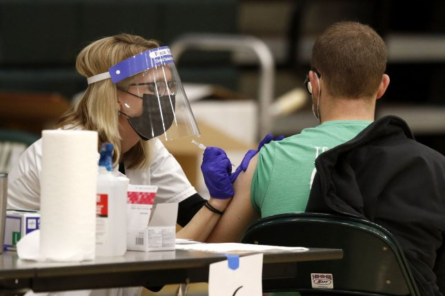 A health care worker administers the coronavirus vaccine to a school staff member in Medina, Ohio, in February. File Photo by Aaron Josefczyk/UPI