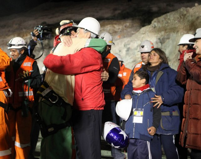 Florencio Avalos, the first of 33 trapped miners to be rescued, hugs Chilean President Sebastian Pinera at the surface of the San Jose Mine near Copiapo, Chile, early Oct. 13, 2010. All of the miners were rescued after spending more than two months underground.. UPI/Chilean Government/HO