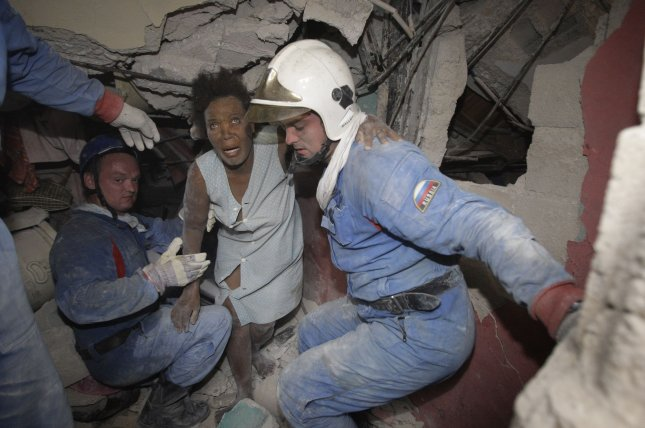 Russian rescuers take a woman victim of the earthquake out of the remains of a house in Port-au-Prince, Haiti on January 16, 2010, after a 7.0 magnitude earthquake caused severe damage. File Photo by Anatoli Zhdanov/UPI
